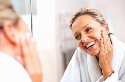 Frau betrachtet sich mit Freude im Spiegel